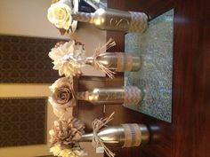 Painted empty wine bottles. Covered with burlap ribbon. Added some raffia and burlap flowers. LOVE!!!