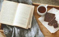 Drinking tea, eating chocolate, reading book.
