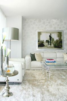 Soft, white low-profile leather furniture complements the velour area rug, transparent coffee table, and subtle silver-patterned wallpaper behind the sofa.
