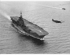 HMS Indomitable, 1943 HMS Indomitable with a Supermarine Seafire Mk. IIC flying overhead, 1943