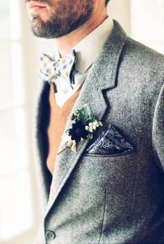 Some dapper men's wedding attire: gray blazer, bow tie and a rustic boutonnière