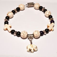 Boho Elephant Charm Bracelet -  This boho bracelet created with white and black magnesite, metal caps and white elephant charm. The magnesite beads are believed to be calming and relaxing. Beaded with care and handmade with strong elastic stretch cord. A perfect bracelet for men and women alike, and works well for any occasion. - $32.00