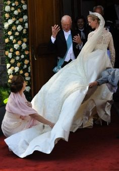 Princess Nathalie of Sayn-Wittgenstein-Berleburg (R) gets help with her dress as her father, Prince Richard of Sayn-Wittgenstein-Berleburg (C) gestures during their arrival for her religious wedding with German Alexander Johannsmann at the Evangelical Church of the castle in Bad Berleburg, Germany, 18 June 2011.