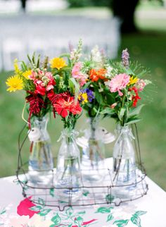 bright flowers in a drink caddy with a vintage tablecloth