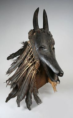 Africa | Goat mask ~ 'Je' ~ from the Guro or Baule people of the Ivory Coast | Wood, feathers, cotton and sacrificial materials | ca. 19th - 20th century