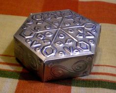 An embossed hexagonal box from an aluminium can for table decor. Could also use embossed metal in other decorative ways