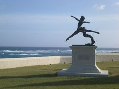 Grand Jete with surf breaking on the coral reef.  The limestone wall is essential. Limestone Wall, Barbados, Crane, Statue Of Liberty, Gymnastics, Places Ive Been, Caribbean, Natural Beauty, Dancing