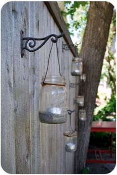 Outdoor lighting with mason jars. Kind of a cool idea. I think maybe even painting the outside of these different colors would make it look really neat at night!