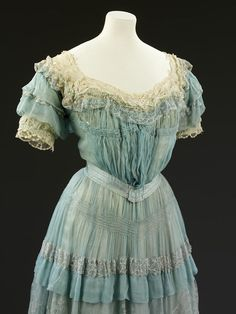 Carresaute designed by Lucile, made in London, 1905. Two-piece evening dress, bodice and skirt, blue silk chiffon, lavishly trimmed with cream lace, pink silk ribbon rosebuds, metallic embroidery, and self-fabric ruffles. Detail of bodice. Victoria and Albert Museum.