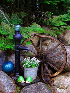 Wagon wheel  water pump...minus the crystal ball things. In the corner by the chimney with two bushes behind the pump side.