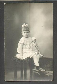 Vintage photo of a little girl with her Red Cross Nurse doll.