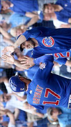 Kris Bryant and Matt Szczur celebrate after scoring runs in the seventh inning…