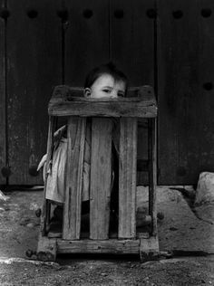 Christer Strömholm. Cuenca, Spain, 1961;  A TODDLER in an insane asylum. And in a cage. How insane is that!!??