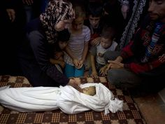 The family of two years and eight months old Palestinian girl Jud Al-Danaf mourn over her body in Gaza City. The Palestinian child died after she was seriously wounded along with four other people the previous day when a rocket fired at Israel fell short and landed inside Gaza - 2014-06-25