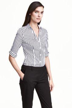 Camisa elástica: Camisa entallada en mezcla de algodón elástico. Mangas largas, pequeño cuello inglés con abertura de pico, y botones delante y en los puños. Interior de los puños y del cuello en color de contraste.