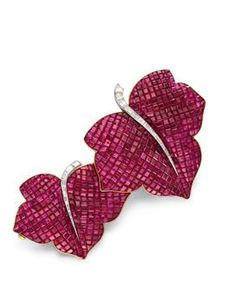 Designed as two calibré-cut ruby laurel leaves, enhanced by calibré-cut diamond stems, mounted in platinum and 18k gold, 1936, with French assay marks and maker's marks, in a Garrard blue leather fitted case. Signed Van Cleef & Arpels