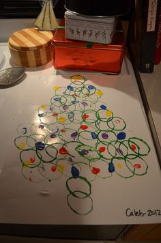 "Christmas tree craft with the end of a paper towel tube and your children's finger prints as the ""lights"" :-)"