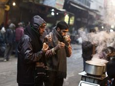 People drink tea at a roadside tea stall - North India shivers in extreme cold | The Economic Times