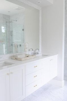 Chic master bathroom features a white floating double vanity accented with brass hardware topped with white quartz fitted with his and her sinks and modern faucets under a marble framed mirror alongside a marble tiled floor.