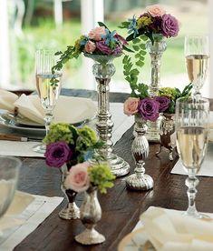 Os castiçais de prata, aqui, não servem para apoiar velas, mas flores