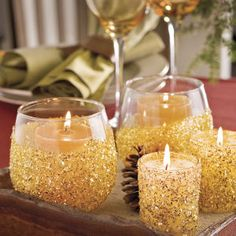 Dip a handful of glass votive holders in glue, roll them in gold glitter, and than insert candles.../