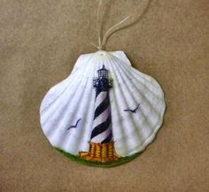 """Very attractive lighthouse scene painted on a 4 1/2"""" clam shell. With two birds flying and a hint of glitter, this ornament will add some sparkle to your Christmas tree."""
