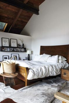 Love the simplicity of a white bedroom with warm wood tones and black and white artwork