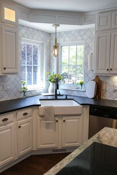 White Modern Farmhouse Kitchen With Corner Apron Sink And Black Granite.  Marble Arabesque Tile To
