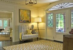Design Ideas: Beautiful Foyer With Geometric Rug. tree legs floor lamp. floral patterned rug. tufted wingback chair. abstract painting. classic foyer.