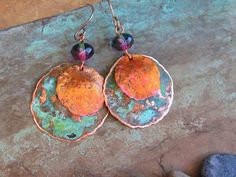The metal disks has been cut from a quality grade copper sheetmetal, hammered, textured, slightly domed and given a touches of patina to create the