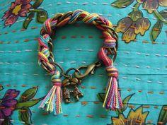Pulseira de corrente de metal ouro velho trançado com linhas coloridas e pingente de namorados com aplicação de strass Swarovski marrom. R$33,90