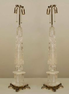 Pair of Continental Baltic 'Neo-Classic' Style  Rock Crystal Obelisk Shaped Table Lamps having an upward-ward tapering square column resting on Silvered Bronze square base with lion-head sphinxes. XXth Century