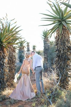 With a backdrop of tall aloes, this shoot is a lovely marriage between earthy and glam: a palette of mixed neutrals with a touch of shimmery copper; succulents and seed pods with elegant white orchids; a table for two in the bushveld laid with vintagey luxe decor; a serving of champagne.