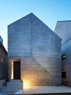 13 Modern House Exteriors Made From Concrete | The way the concrete has been joined on the front of this house gives it a geometric look that's only interrupted by the cutout for the door.