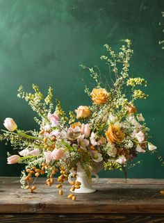 Yellow palm dates, white spirea blossoms, golden roses, pink tulips and pink hellebores look lush and wild in this Putnam & Putnam arrangement.
