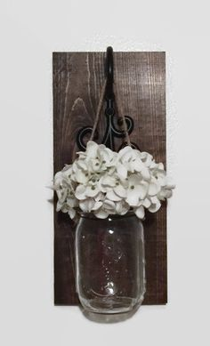 The Mason jar hangs from jute that is attached to wire. The jar band is painted. This item would look great in any room in your home.