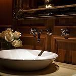 Wood paneled bathroom with white vessel sink.
