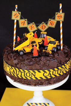 A Construction Themed Birthday Party with Oreo cookie dirt chocolate cake, safety cone candles, dump truck lollipops+ truck-shaped cookies with glitter coal