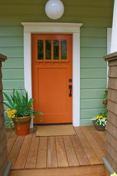 This bright orange door's sturdy structural elements stay true to the home's Craftsman style. While the home's exterior is a sage green hue, designer John Gidding swings to the other side of the color wheel for a front door color with true contrast.