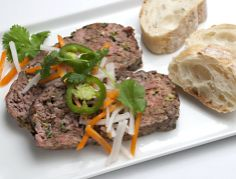 Banh Meatloaf - Pork and beef meatloaf is flavored with basil, scallions, garlic and Chinese five-spice powder, topped with pickled carrots and daikon, then served with baguette slices for this American take on Vietnamese bánh mì sandwiches.