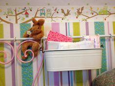 Wickelstation aus einem IKEA-Balkonkasten an der Bettrückwand des rosa-weiß umlackierten Metallbettes (Glücksfund bei ebay Kleinanzeigen) aufgehängt. Den Hasen habe ich auf meinem Junggesellinnenabschied beim Torwand schießen gewonnen  schönes Mulltuch mit kleinen Vögelchen von Name it
