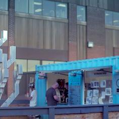 Glåss bar laitier, une entreprise aux couleurs de CULTURAT dans un aménagement urbain exposant l'oeuvre de Claude Bérubé.