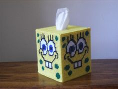 Adore this Sponge-Bob bright yellow smiley face tissue box cover in your little ones bedroom. His smiley face is on all four sides.  Colors: Yellow, Blue,Green, White and Black. I used: worsted weight acrylic yarn and plastic Canvas.