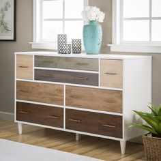 Mid-century modernism meets striking functionality with the Christian 8-drawer dresser. This large white veneer dresser is set with drawers of various wood veneers and sizes. Drawer front veneers are