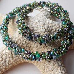 Amazing bead encrusted necklace -deep green with elements of gold copper tanzanite and mauve. Each bead has been hand threaded