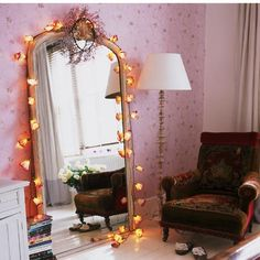 Fairy lights decorate a floorstanding mirror and vintage armchair  Every bedroom is an escape – especially when you're studying – so create an area for a shabby-chic armchair so that all that textbook reading is more comfortable. Make sure there's suitable lighting, like this spindle-base floor lamp, and a giant mirror (draped with pretty fairy lights) will reflect even more light.