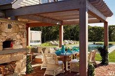 Under the terrace pergola, a zinc-top reclaimed-oak table by Mecox is surrounded by Janus et Cie chairs cushioned in a Perennials fabric; the chaise longues beside the pool are by Sutherland.