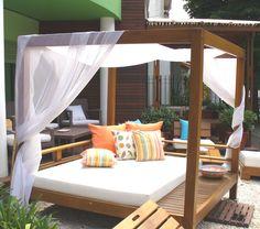 Camastro Bali, con un cómodo colchón que deja deja un espacio del mueble a modo de mesa. Con almohadones de colores vibrantes.