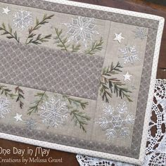 """A Scattering of Snow - table mat"" pattern by Melissa Grant of One Day in May - A small Christmas project featuring embroidered snowflakes, scattered amongst variegated pine branches."