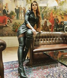 Amateur brunette seated on couch in black leather minidress and thigh boots